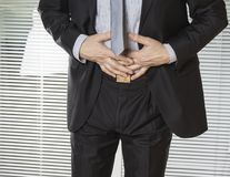 Businessman holding his stomach in pain with stomachache or indigestion. Businessman holding his stomach in pain with stomachache or indigestion Stock Image