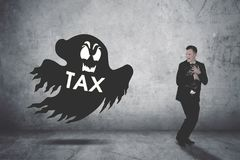 Businessman running scare being chased by a tax ghost. Businessman holding his suitcase running scare being chased by a tax ghost royalty free stock photography
