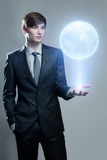 Businessman holding hologram of the earth Stock Photography