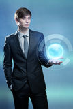 Businessman holding hologram of the earth Stock Photo