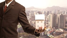 Businessman holding home model with cityscape background. Loan concept royalty free stock photography