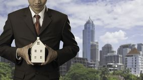 Businessman holding home model. With cityscape background, Loan concept stock photography