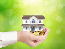 Businessman holding home model and coins Stock Image