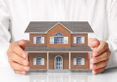 Businessman holding home model Stock Photos