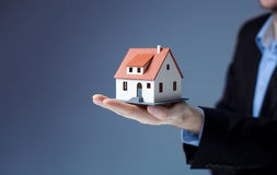 Businessman holding home model. Loan concept stock photo