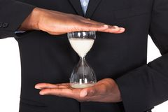 Businessman holding hourglass Stock Images