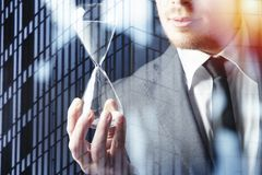 Businessman holding a hourglass. Concept of deadline in business. Businessman holding a hourglass in hand. Concept of deadline in business stock images