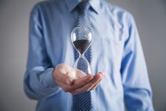 Businessman holding hourglass. Deadline concept royalty free stock photo