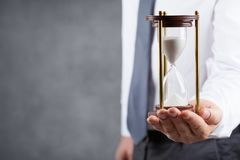 Businessman holding hourglass in his hand. Deadline and time management concept. Businessman holding hourglass in hand. Deadline and time management concept royalty free stock photos