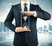 Businessman holding hourglass at megapolis city background, time Stock Photo