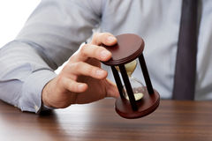 Businessman holding hourglass. Stock Photos