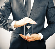 Businessman holding hourglass, time concept Royalty Free Stock Images