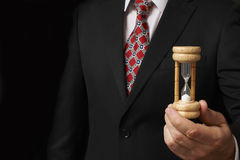 Businessman holding hourglass. Towards camera with space for copy stock photography