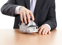 Businessman holding house architectural model stock photo
