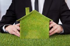 Businessman holding house of grass Stock Photo