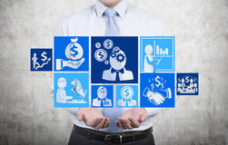 Businessman holding icons. Businessman holding business icons on gray background Stock Images