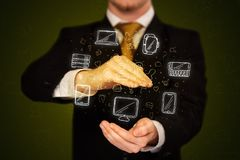 Businessman holding networking icons. Businessman holding icons related to devices and communication Royalty Free Stock Photography