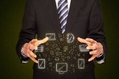 Businessman holding networking icons. Businessman holding icons related to devices and communication Stock Image