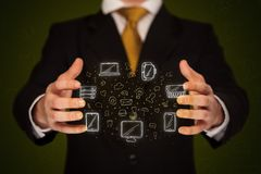 Businessman holding networking icons. Businessman holding icons related to devices and communication Stock Images