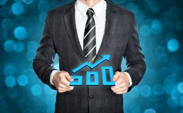 Businessman holding an increasing digital chart. Businessman in a dark suit is holding a rising chart symbol in both hands Stock Images