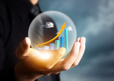 Businessman holding increasing graph in crystal ball Stock Images