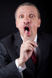 Businessman holding index finger at his mouth Royalty Free Stock Images