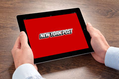 Businessman holding iPad with New York Post on the screen Royalty Free Stock Images