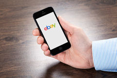 Businessman holding iPhone with eBay on the screen over the vill Stock Photography