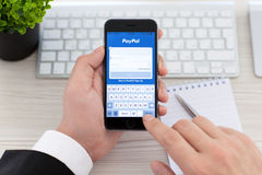 Businessman holding iPhone 6 Space Gray with service PayPal Royalty Free Stock Images