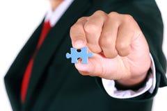 Businessman holding jigsaw Stock Images