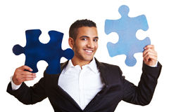 Businessman holding jigsaw pieces. Happy businessman holding two blue jigsaw pieces Royalty Free Stock Images