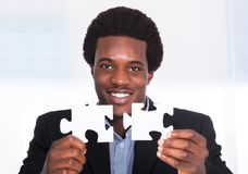 Businessman Holding Jigsaw Puzzle Royalty Free Stock Photos