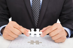 Businessman holding a jigsaw stock images