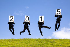Businessman holding 2015 and jumping on a meadow Stock Images