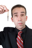 Businessman Holding Key. A young businessman wearing a suit, holding an old key, isolated against a white background Royalty Free Stock Photo