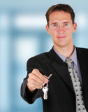 Businessman holding key in his hand to hand it over Stock Photos