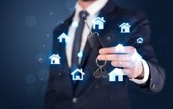 Businessman holding keys with houses around Stock Images