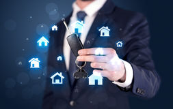 Businessman holding keys with houses around Stock Image