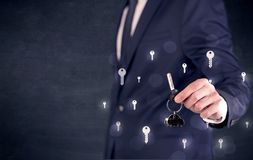 Businessman holding keys with keys around Stock Photography