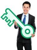 Businessman holding keys symbol Royalty Free Stock Photo