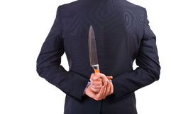 Businessman holding knife behind his back. Business man holding knife behind his back Stock Photography