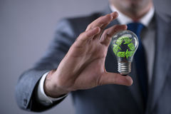The businessman holding lamp in green environment concept royalty free stock images