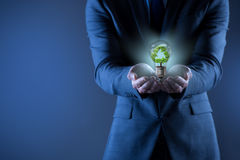 The businessman holding lamp in green environment concept Royalty Free Stock Image