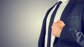 Businessman holding the lapel of his jacket Royalty Free Stock Images