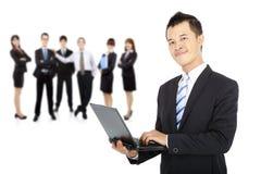 Businessman holding laptop. Smiling businessman holding laptop and successful business team Royalty Free Stock Images