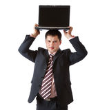 A businessman is holding the laptop above his head Royalty Free Stock Images