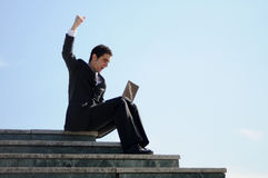Businessman holding a laptop computer. A businessman holding a laptop computer with his arm up Stock Image