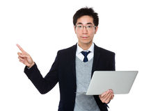 Businessman holding with laptop computer and finger pointing up Stock Images