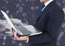 Businessman holding laptop with connecting icons and cloud in background. Digital composition of businessman holding laptop with connecting icons and cloud in royalty free stock photography