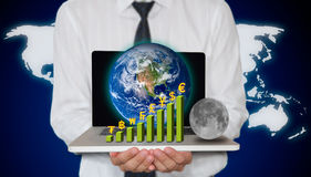 Businessman holding laptop with currency graph. And small planet Royalty Free Stock Photos